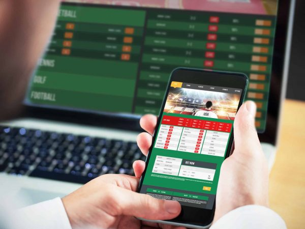 Businessman using smartphone against gambling app screen