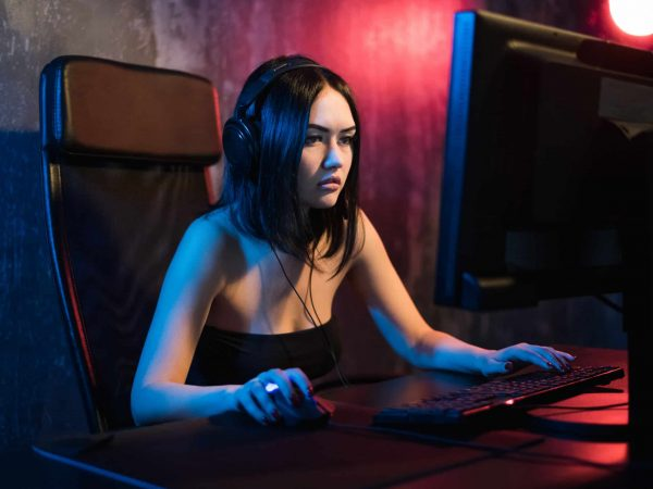 A cute female gamer girl sits in a cozy room behind a computer and plays games. Woman live streaming computer video games to her fans. Streamer and gamer concept.